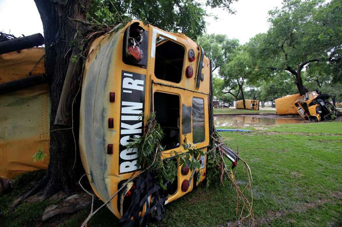 """METRO Buses from Rockin' """"R"""" River Rides are wrapped around trees along the banks of the Guadalupe in Gruene. Flooding in New Braunfels on June 9, 2010. Tom Reel/Staff"""