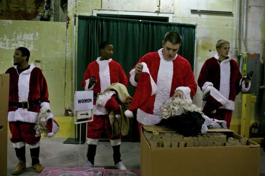 METRO - Elf Louise volunteers, from left, Christian Forney and Yamell Valencia, both with Top Teens of America, Rivercity Chapter, and Tanner Foster and Ben Scott, both with Stevens ROTC, get dressed to deliver presents to families in San Antonio on Tuesday, Dec. 18, 2008. LISA KRANTZ/lkrantz@express-news.net Photo: LISA KRANTZ, Lkrantz@express-news.net / SAN ANTONIO EXPRESS-NEWS