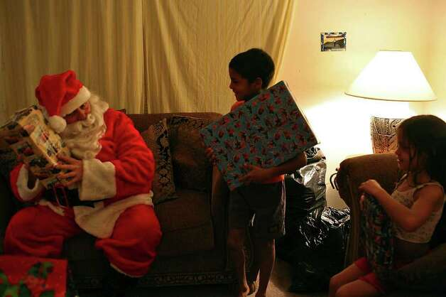 METRO - Elf Louise volunteer Bob Branson delivers presents to Juan Maldonado, 9, and his sister, Natashjia Maldonado, 7, at their home in San Antonio on Tuesday, Dec. 18, 2008. LISA KRANTZ/lkrantz@express-news.net Photo: LISA KRANTZ, Lkrantz@express-news.net / SAN ANTONIO EXPRESS-NEWS