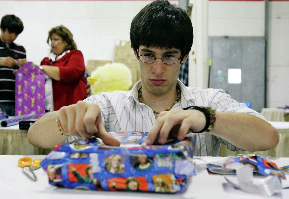 FOR SALIFE - Andrew Wyble put a name tag on a gift after wrpping Monday Dec. 8, 2008 part of the Elf Louise Project. (PHOTO BY EDWARD A. ORNELAS/eornelas@express-news.net) Photo: EDWARD A. ORNELAS, SAN ANTONIO EXPRESS-NEWS / eornelas@express-news.net