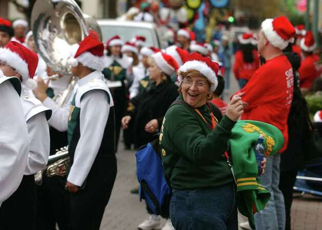 METRO - Ilda Lopez gets down to the sounds of the Holmes High School marching band Saturday, December 7, 2002 during the annual Children Giving to Children Parade and Toy Drive o benefit the Elf Louise Christmas Project. Lopez's son and nephew were playing in the band. BAHRAM MARK SOBHANI/STAFF Photo: BAHRAM MARK SOBHANI, SAN ANTONIO EXPRESS-NEWS / SAN ANTONIO EXPRESS-NEWS