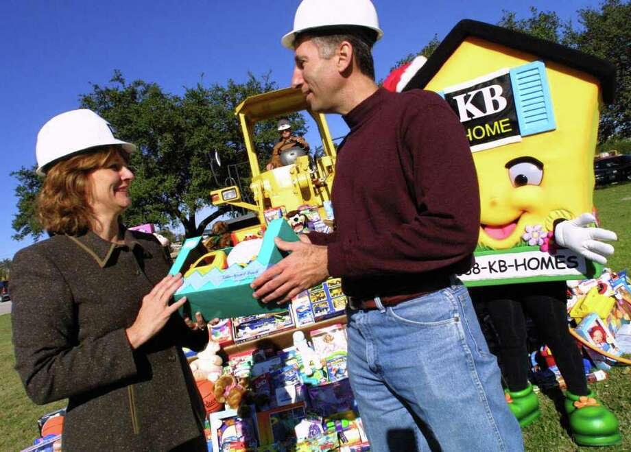 "DAILY FOR METRO-- ""Elf Louise,"" aka Louise Locker Hall, accepts a  front-end loader full of toys from KB Home CEO Dave Matlock (at KB Home corporate headquarters) Friday Dec. 14, 2001 as part of her annual toy drive for the holidays.  Matlock later detailed KB Home's Second Annual Toy Drive and the home builder's continuing committment to the Elf Louise Christmas Project.  Rick Hunter/Staff Photo: Rick Hunter/ Express-News File Photo"