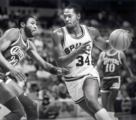 Mike Mitchell of the San Antonio Spurs drives on Rory White of the Los...