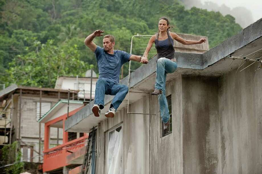 "Brian O'Conner (PAUL WALKER) and Mia Toretto (JORDANA BREWSTER) run for their lives in a reunion of returning all-stars from every chapter of the explosive franchise built on speed--""Fast Five."" Photo: Contributed Photo / Norwalk Citizen"