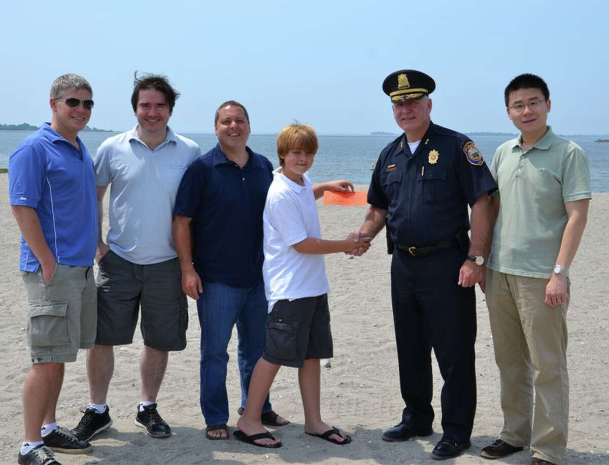 Police Chief Al Fiore presents the first ticket to the Independence Day Fireworks Celebration to Paul Friezo at Compo Beach. Also pictured, from left, are: Mark McKeown, Tom Kennedy, David Friezo and Bing Cui.