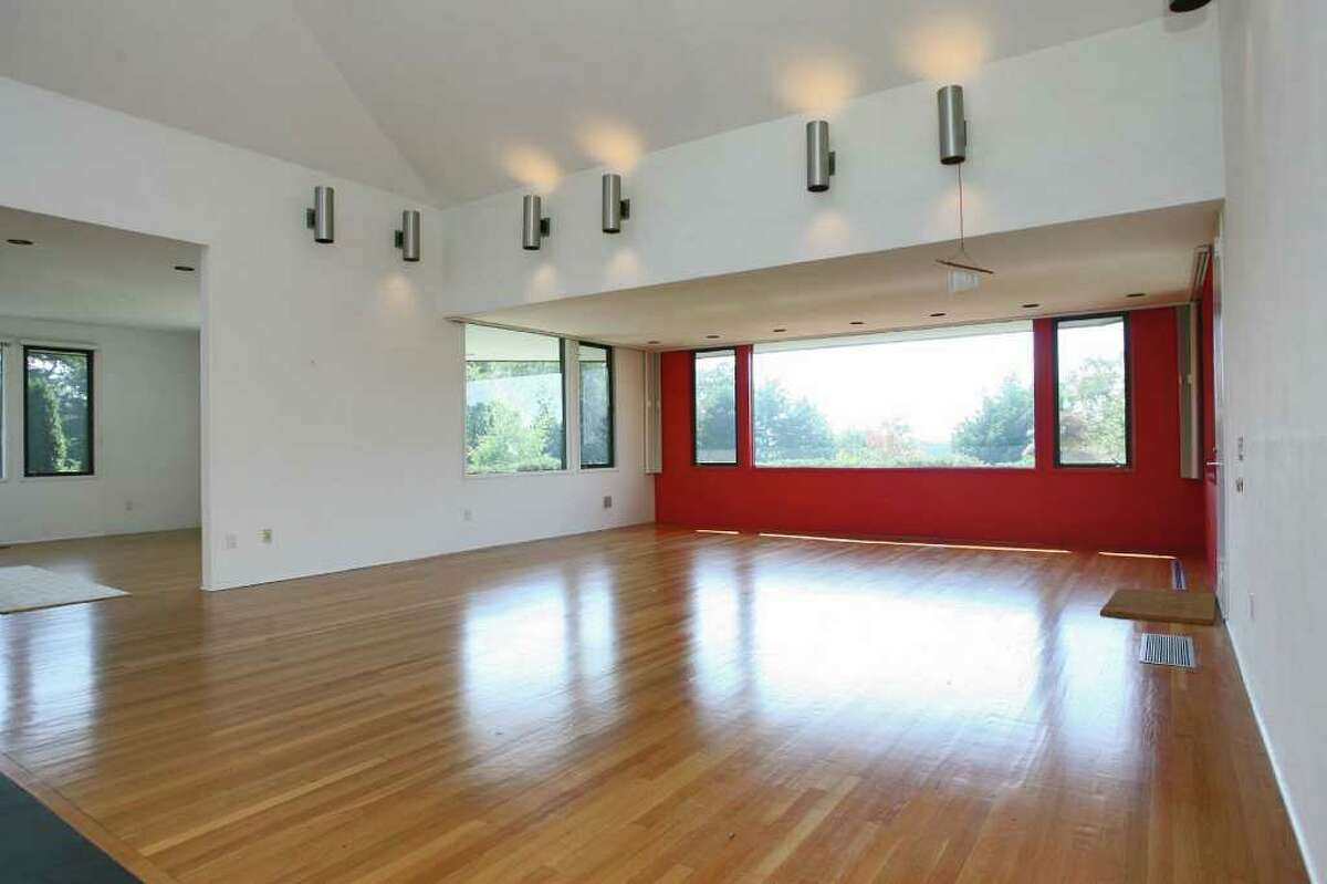 The contemporary home's spacious great room features a floor-to-ceiling fireplace and a vaulted ceiling.