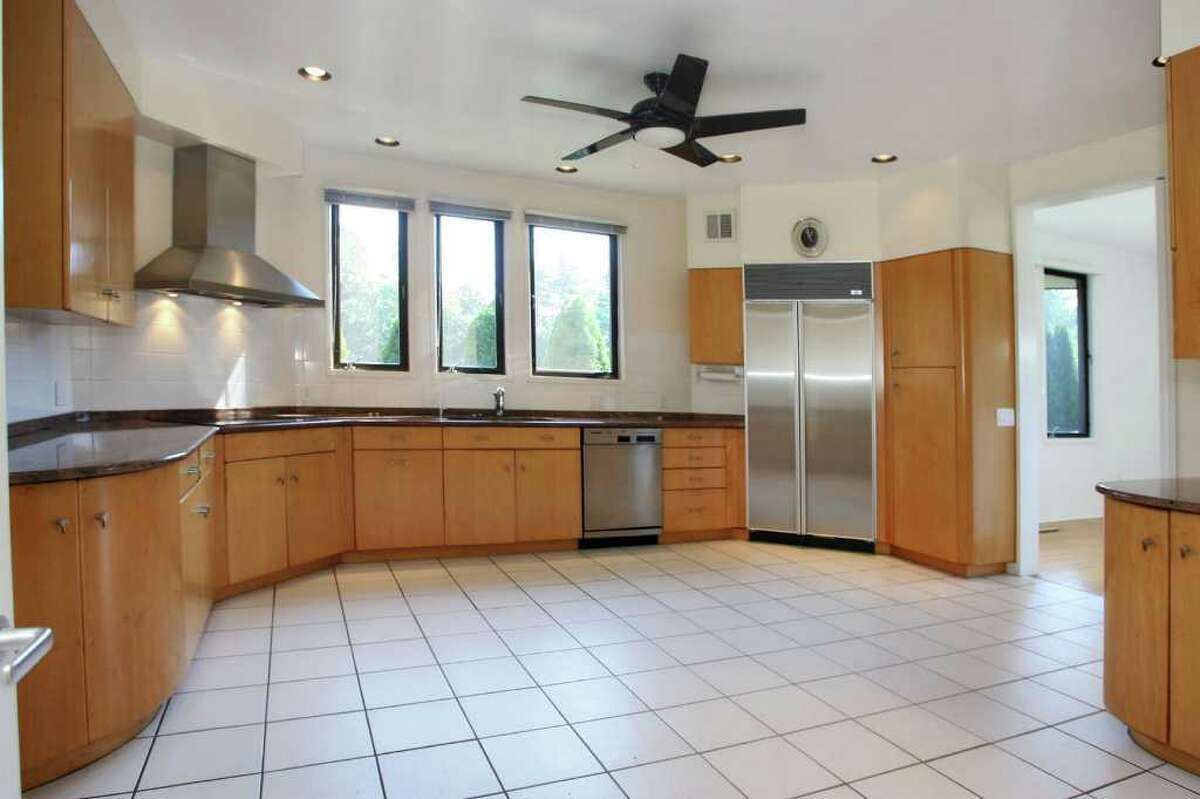 The kitchen has been updated and features a white ceramic-tile floor, granite counter, eat-in section, Rutt cabinetry, a Sub-Zero refirgerator, Thermador double, wall-mounted ovens and Bosch dishwasher.