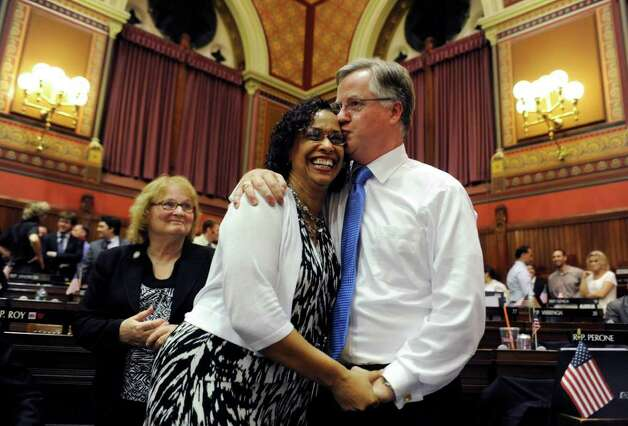 House Majority Leader Brendan Sharkey, D-Hamden, right, kisses Toni Walker D-New Haven as Peggy Sayers, D-Windsor, left, looks on at the close of the legislative session at the Capitol in Hartford, Conn., early Thursday, June 9, 2011. (AP Photo/Jessica Hill) Photo: Jessica Hill, AP / AP2011