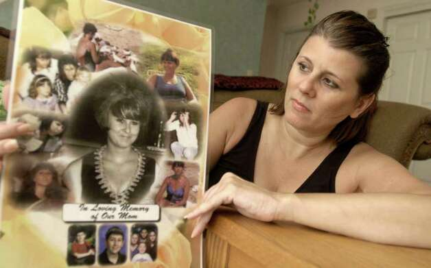 In this file photo Sherrie Passaro, of Danbury holds a poster of photographs in memory of her mother, Mary Badaracco, who disappeared from her home nearly 27 years ago. Photo: Carol Kaliff / The News-Times