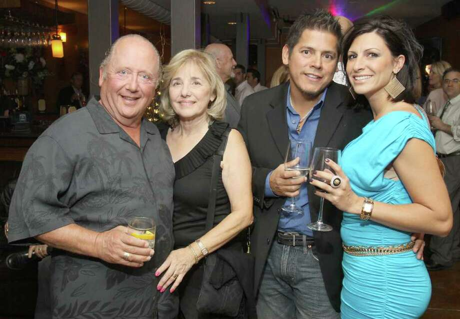 "Saratoga Springs, NY - June 3, 2011 - (Photo by Joe Putrock/Special to the Times Union) - (l to r)Saratoga Builders, LLC Partner Sam Palazzole, Linda Palazolle, artist Frankie Flores and Ann-Marie Flores during ""Win a Vette, Save a Vet"", a benefit for Guardian House. Frankie Flores was commision to do all of the paintings that decorate the paddock Lounge. Photo: Joe Putrock / Joe Putrock"