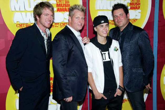Jay DeMarcus, left, Gary LeVox, Justin Bieber, and Joe Don Rooney arrive at the 2011 CMT Music Awards in Nashville, Tenn. on Wednesday, June 8, 2011. (AP Photo/Charles Sykes) Photo: Charles Sykes