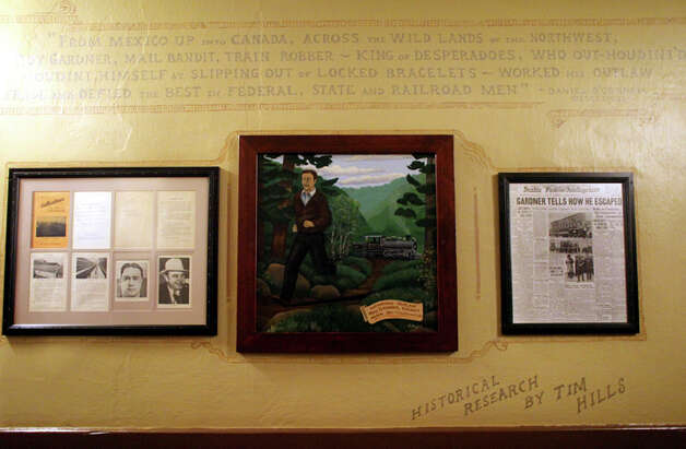 A painting and other artifacts, including a front page of the Seattle Post-Intelligencer from 1921, line a wall at the Olympic Club Hotel in Centralia, Wash. In 1921, notorious outlaw Roy Gardner -- who later escaped from  McNeil Island prison -- was captured at the Olympic Club in Centralia. Photo: Joshua Trujillo/seattlepi.com