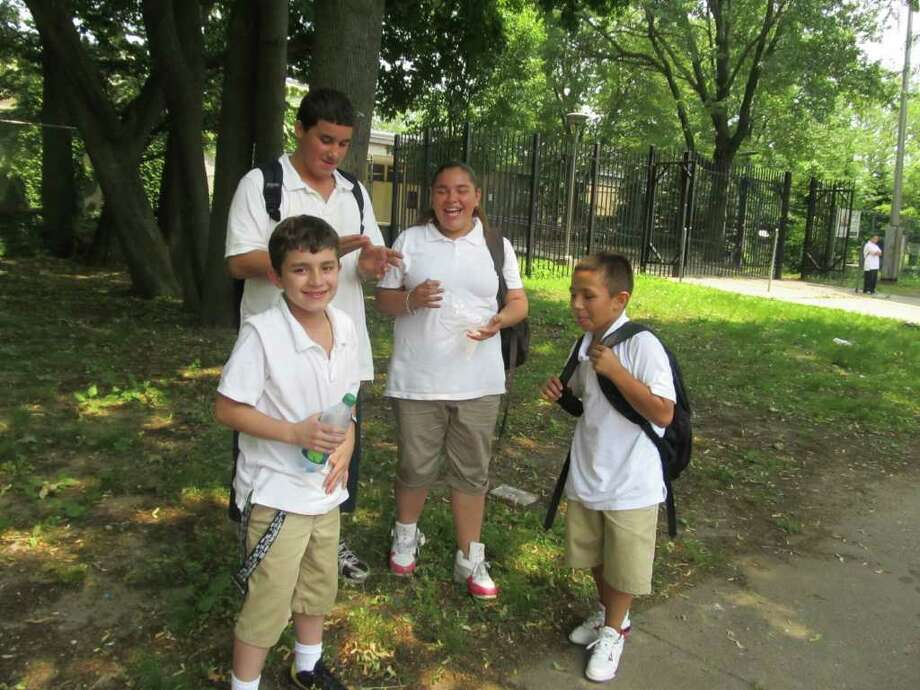 Outside Roosevelt School in Bridgeport after the school closed at 1:20 p.m. Thursday are, from left, studetns Dominick Rosado, David Rosado, Natalia Rosado and Jonathan Duarte. Photo: Stephanie Paulino / Connecticut Post freelance