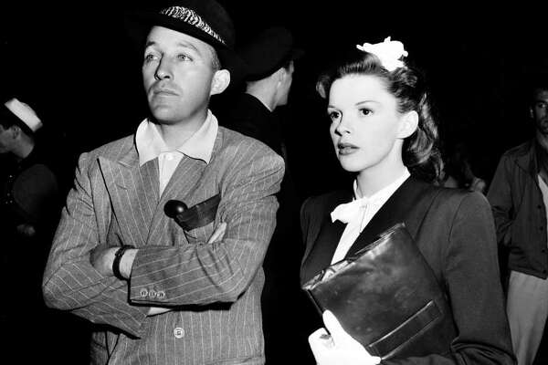 "Singer-actor Bing Crosby, left, visits singer-actress Judy Garland on the set of ""The Harvey Girls"" in Hollywood, Ca., in 1945."