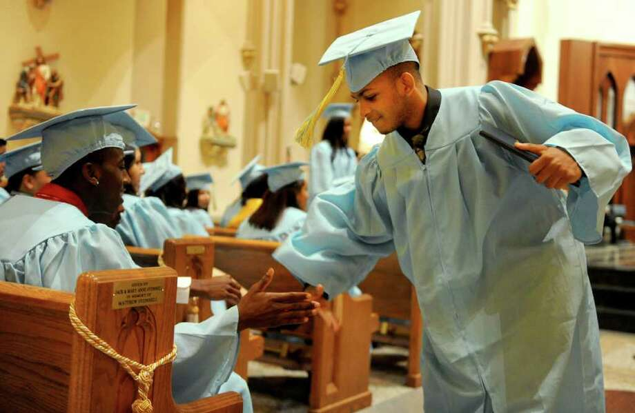 Calvin Wade gets a high-five after getting his diploma during Thursday's graduation ceremony for Kolbe Cathedral High School Seniors at St. Augustine Cathedral in Bridgeport on June 9, 2011. Photo: Lindsay Niegelberg / Connecticut Post