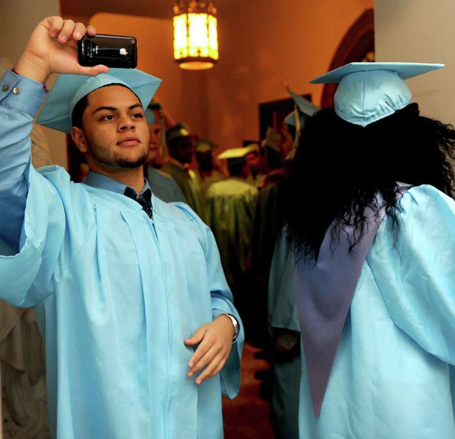 Alex Fajardo takes a picture before Thursday's graduation ceremony for Kolbe Cathedral High School Seniors at St. Augustine Cathedral in Bridgeport on June 9, 2011. Photo: Lindsay Niegelberg / Connecticut Post