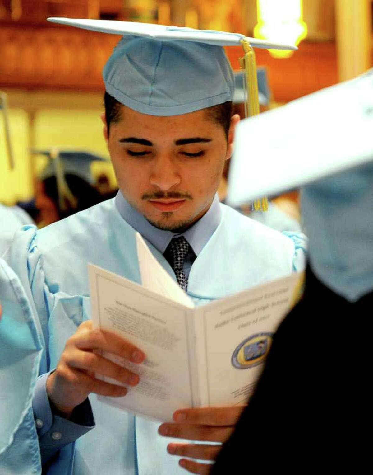 Jeffrey Falberg reads the program during Thursday's graduation ceremony for Kolbe Cathedral High School Seniors at St. Augustine Cathedral in Bridgeport on June 9, 2011.