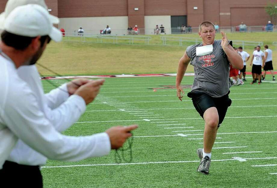 Lamar coaches Todd Whitten and Nathen Reves, foreground, time James McCormick during the Cardinal's football camp for high school players. Guiseppe Barranco/The Enterprise Photo: Guiseppe Barranco