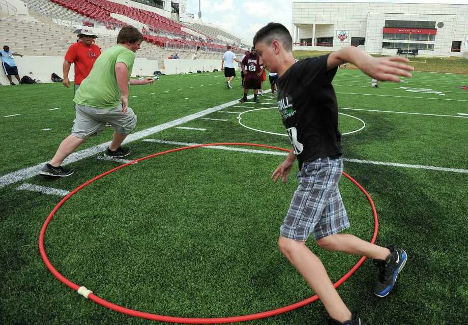 Sam Collier, right, chases one of his friends around a hoop during Lamar's summer football camp on Thursday. Guiseppe Barranco/The Enterprise