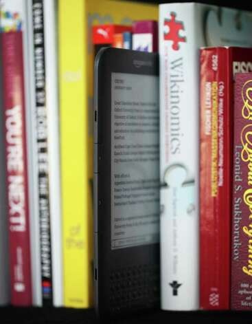 A Kindle 3G electronic book reader, by Amazon.com Inc., stands between a row of books in this arranged photograph in London, U.K., on Thursday, March 24, 2011. Amazon has sent emails to small partner retailers in Connecticut telling them they will be ending their relationship because of the controversial online sales tax passed by the state legislature. Photographer: Chris Ratcliffe/Bloomberg Photo: Chris Ratcliffe, Bloomberg / © 2011 Bloomberg Finance LP