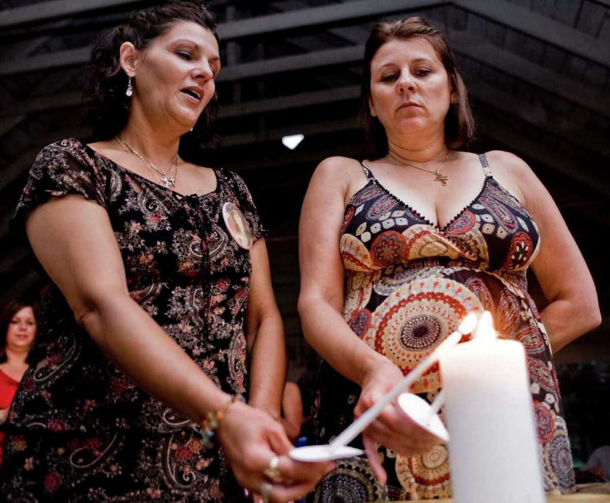Sisters Beth Protefa of Torrington and Sherrie Passaro of Danbury light candles during a 2009 prayer vigil for their mother, Mary Badaracco. The vigil was held to observe the 25 years since Badaracco's disappearance.