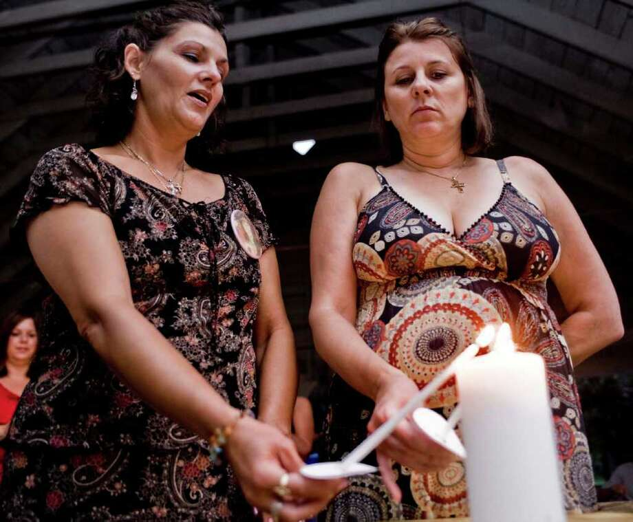 Sisters Beth Protefa of Torrington and Sherrie Passaro of Danbury light candles during a 2009 prayer vigil for their mother, Mary Badaracco. The vigil was held to observe the 25 years since Badaracco's disappearance. Photo: Scott Mullin / The News-Times