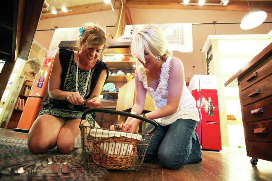 Brandi Dunagan, left, and Maggie Clifton of Country Sugar Events look through a basket of vintage silverware June 2, 2011, at Back Alley Antiques in the shops at Artisans Alley. Dunagan said she was inspired to start planning sustainable weddings after seeing how much was spent and wasted in some high-priced weddings.  ANDREW BUCKLEY / abuckley@express-news.net Photo: ANDREW BUCKLEY, SAN ANTONIO EXPRESS-NEWS / SAN ANTONIO EXPRESS-NEWS