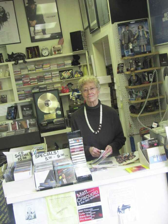 "Pictured is Sally White, the owner of Sally's Place, a music shop on Main Street in downtown Westport. Behind White is a ""gold record"" given to her in 2009 by the Westport Arts Center ""for her dedication to perpetuating musical taste in appreciation of her golden ears and golden heart."" Photo: Contributed Photo / Westport News"