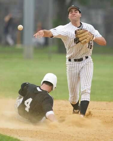 Danbury shortstop Kyle Convissar turns a double play against the Mystic Schooners Friday night at Rogers Park. Photo: Barry Horn / The News-Times Freelance