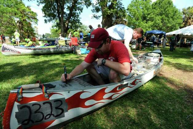 "Stephen Tatum prepares his canoe on Friday, June 10, 2011, for Saturday's Texas Water Safari canoe race.  ""It seems like something crazy to do. It'll be fun and an experience of a lifetime,"" he said. Canoers will paddle for 260 miles to the Texas Coast. Tatum marks his canoe with a message of support for the Dallas Mavericks, who are participating in the NBA finals. Photo: Billy Calzada/Express-News / gcalzada@express-news.net"