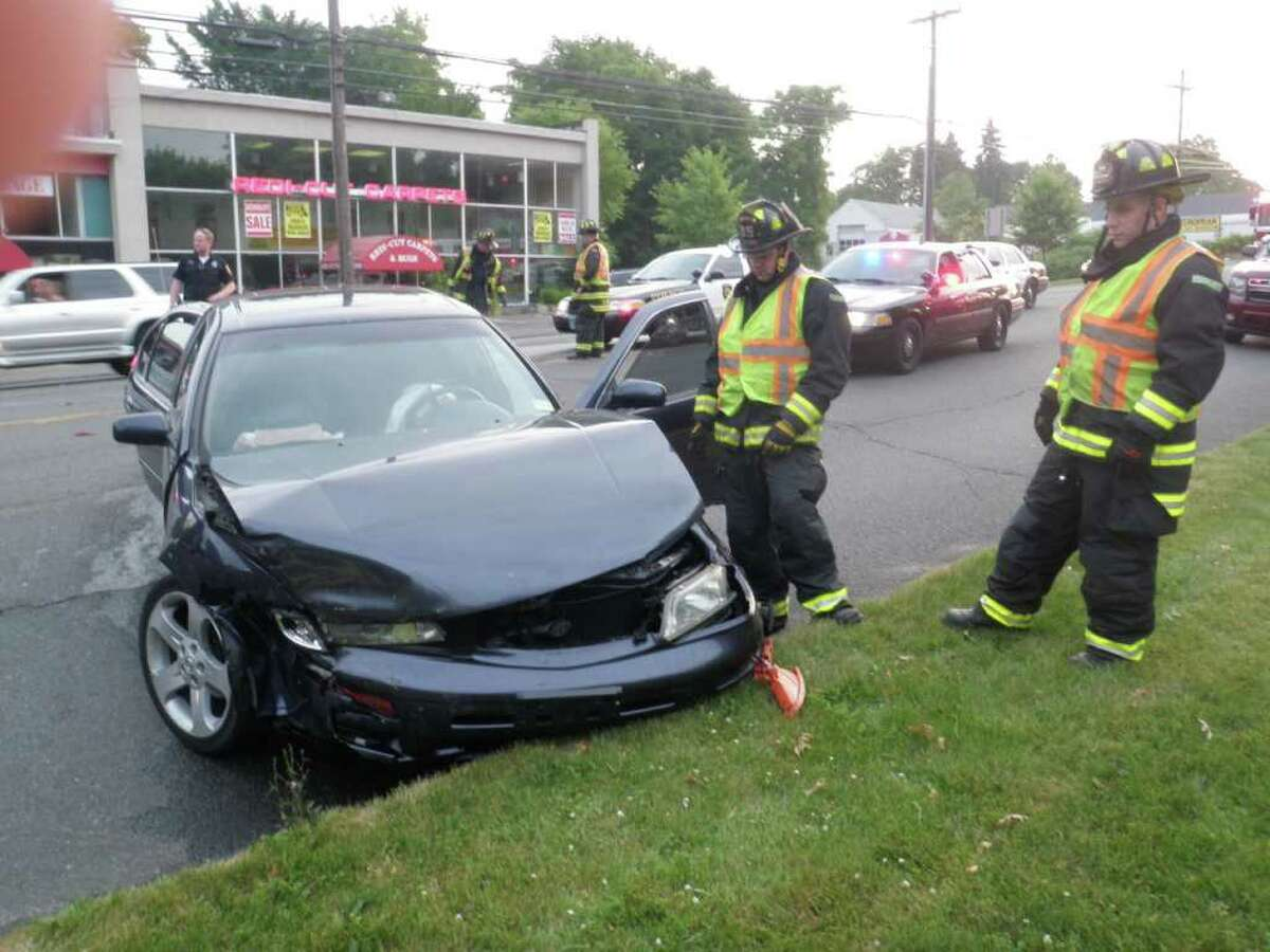 Firefighters examine one of the two cars that collided Friday night on Post Road East.