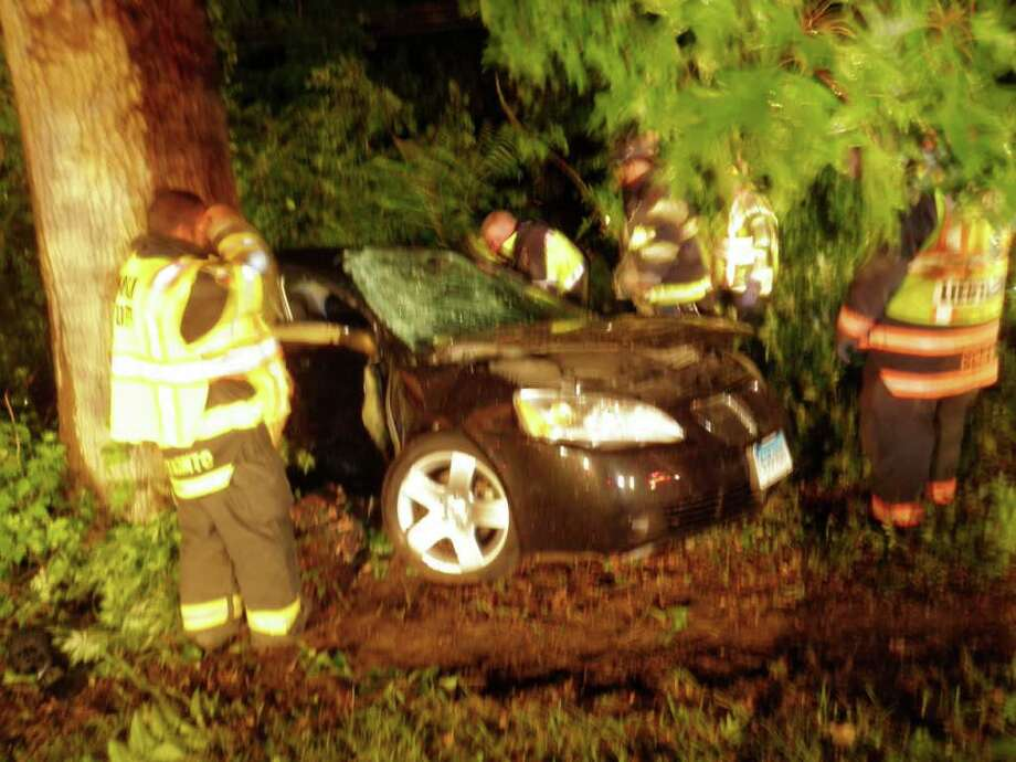 This car's driver had to hospitalized after striking a tree near the Merritt Parkway's southbound Exit 40 early Saturday. Photo: Contributed Photo/Westport Fire Department / Westport News contributed