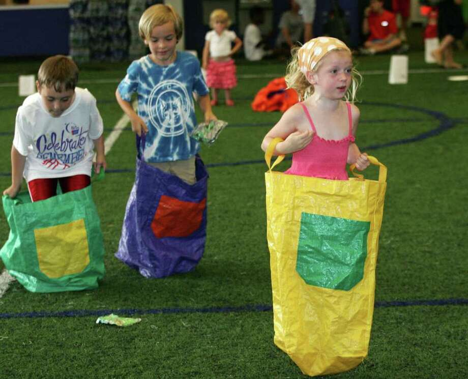 Annabel Woodworth, right, took part in a sack race before the start of the Relay For Life event Friday night, June 10, 2011, at the Sono Field House in South Norwalk. The event was moved from the Brunswick School campus on King Street in Greenwich due to the mountain lion sighting. Photo: David Ames, David Ames/For Greenwich Time / Greenwich Time Freelance
