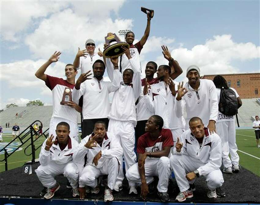 The Texas A&M men's team celebrates with the trophy after winning the team title at the NCAA college outdoor track and field championships, Saturday, June 11, 2011, at Drake Stadium in Des Moines, Iowa. (AP Photo/Charlie Neibergall)