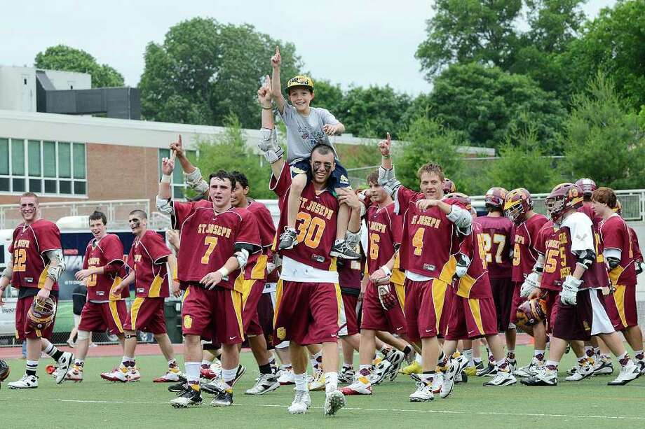 Mike Mulligan, 8, Stratford, rides on the shoulders of his brother Pat Mulligan as St Joseph High School celebrates the win of the Class S boys lacrosse championship versus Joel Barlow High School, at Brien McMahon High School in Norwalk, CT on Saturday June 11, 2011. Photo: Shelley Cryan / Shelley Cryan freelance; Connecticut Post freelance