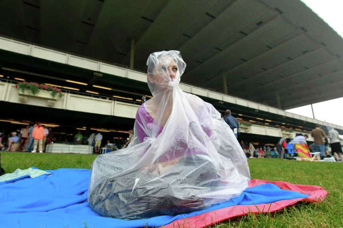 Laurel Olson uses a plastic bag to stay dry before the Belmont Stakes horse race Saturday, June 11, 2011, in Elmont, N.Y. (AP Photo/Julio Cortez)