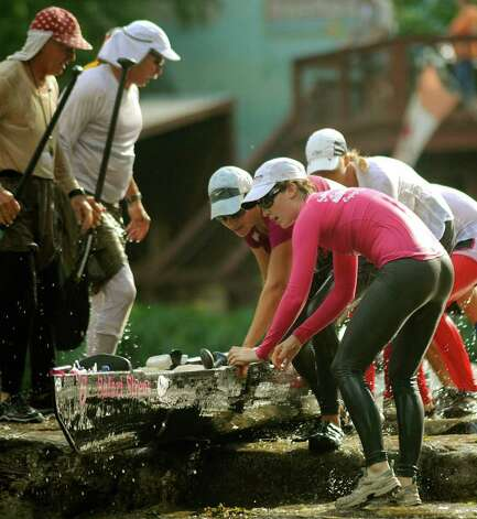 "The ""Safari Sirens,"" an all-female team, work to get their canoe into the water at John J. Stokes Park during the Texas Water Safari, a 260-mile race on rivers from San Marcos to the Gulf Coast. Photo: Billy Calzada/Express-News / gcalzada@express-news.net"