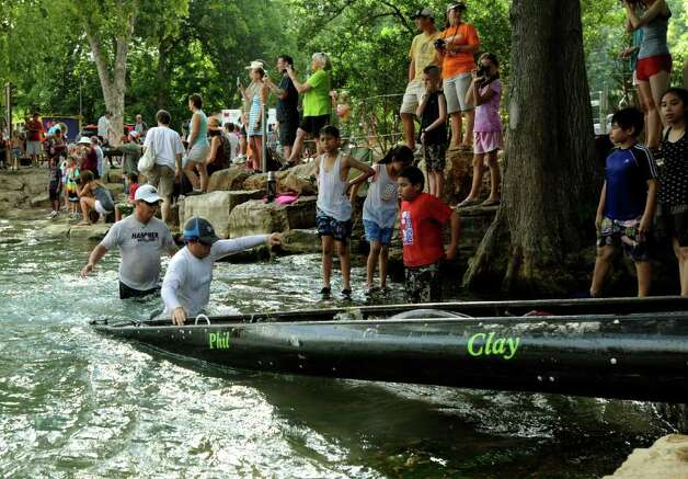 People watch as canoers move their watercraft from water to land in John J. Stokes Park in San Marcos during the Texas Water Safari, a 260-mile race on rivers from San Marcos to the Gulf Coast. Photo: Billy Calzada/Express-News / gcalzada@express-news.net