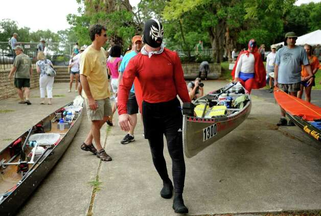 "Joe Mann of the ""Dark  Horse"" team prepares to help put his team's canoe into the San Marcos River at Aquarena Springs in San Marcos in preparation for the start of the Texas Water Safari, a 260-mile race on rivers from San Marcos to the Gulf Coast, on Saturday, June 11, 2011. Photo: Billy Calzada/Express-News / gcalzada@express-news.net"