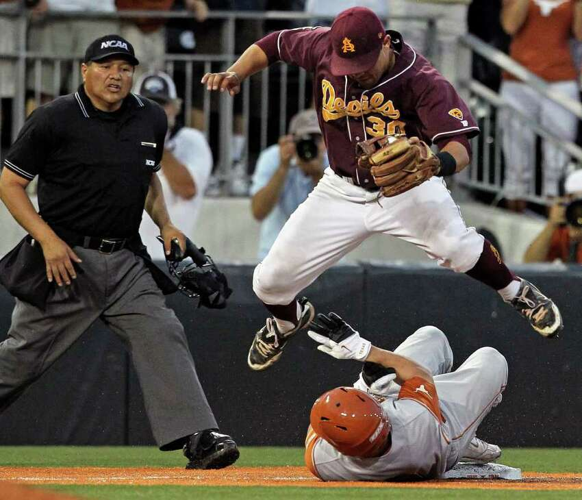Arizona State third baseman Riccio Torrez leaps over the slide of Tant Sheperd who is safe for a triple in the last inning as the Texas Longhorns play Arizona State in game 2 of their super regional playoff series at Disch-Falk Field in Austin on June 11, 2011. Tom Reel/Staff