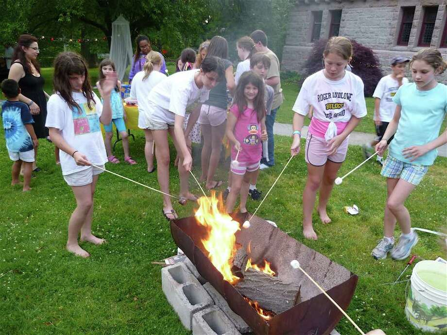 Kids toast marshmallows around a fire pit Friday during the Pequot Library's annual potluck supper/campout on the library's Great Lawn in Southport. Photo: Contributed Photo/Mike Lauterborn, Contributed Photo / Fairfield Citizen contributed