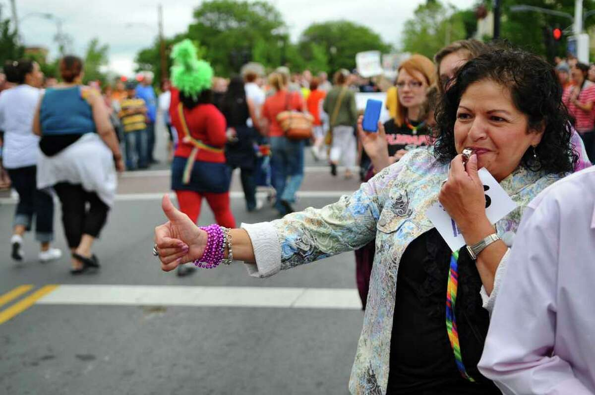 Lourdes Reyes gives thumbs up to marchers on Lark Street during the Capital Pride 2011 Parade & Festival on Sunday, June 12, 2011, in Albany, NY. ( Philip Kamrass / Times Union)