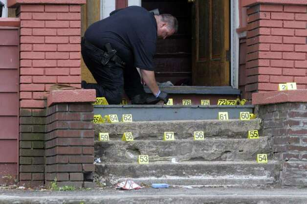 Yellow numbered cards mark different pieces of  evidence as Schenectady police crime scene investigator Detective John Ericson collects evidence at the scene at 730 Bridge St. where the teenager Eddie Stanley was killed on Sunday, June 12, 2011, in Schenectady. (Paul Buckowski / Times Union) Photo: Paul Buckowski