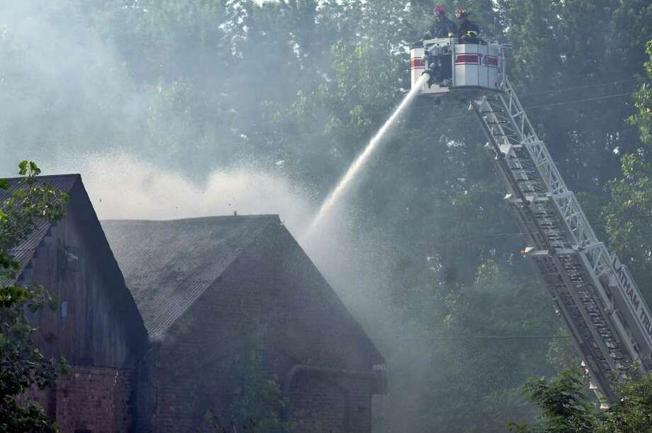 Firefighters direct water onto the scene of an old industrial building on 14th Street on Sunday evening June 12, 2011 in Watervliet, NY.   ( Philip Kamrass / Times Union) Photo: Philip Kamrass
