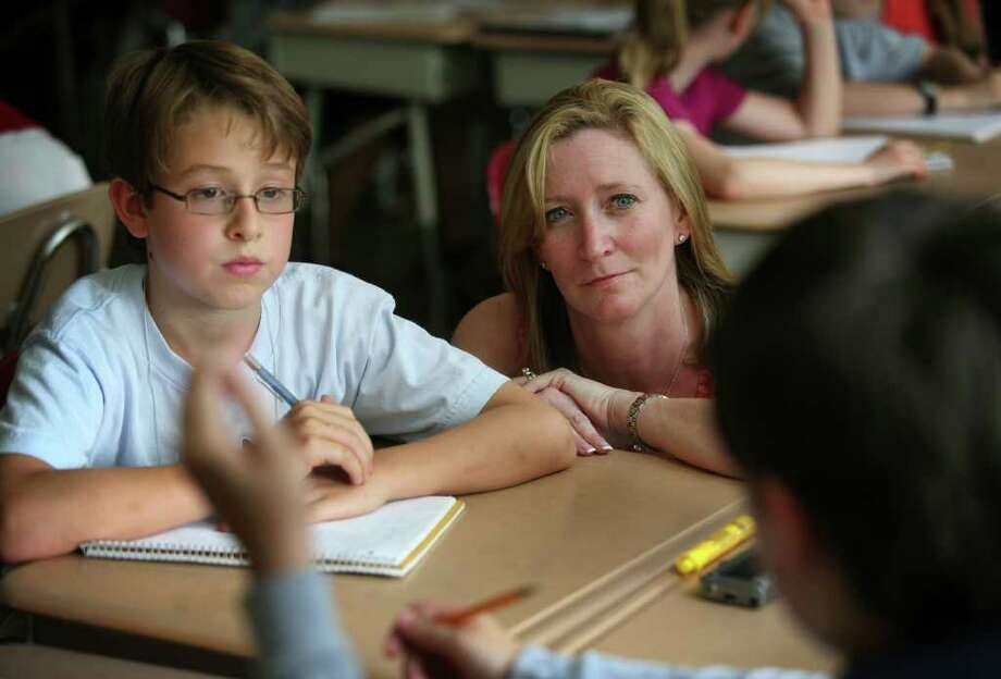 Talented and gifted teacher Michele Molloy listens to a discussion between Nick Williamson, 9, left, and Ali Belizadi, 10, during the Wednesday morning gifted class for fourth graders at Middlebrook School in Trumbull. The students are working on a science project trying to find solutions for declining shore bird and horseshoe crab populations. Photo: Brian A. Pounds / Connecticut Post