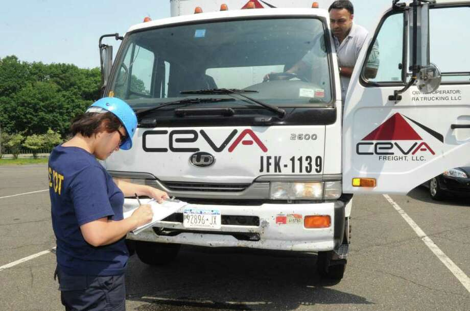 Elaine Chan of the Federal Motor Carrier Safety Administration asks truck driver Dave Atwal, of Hicksville, N.Y., to turn on the lights on the truck at the Greenwich weigh station on Interstate 95 on Wednesday, June 8, 2011. Photo: Helen Neafsey / Greenwich Time