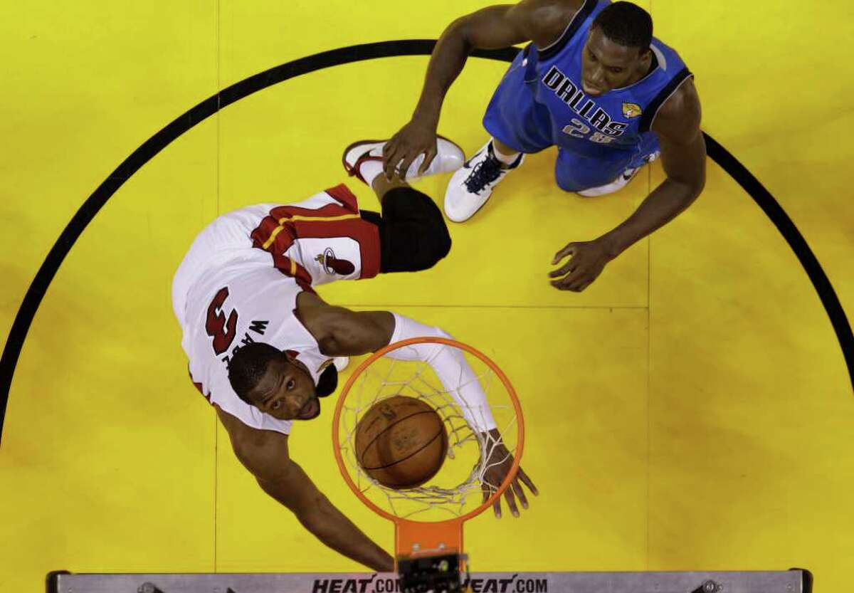 Miami Heat's Dwyane Wade shoots past Dallas Mavericks' Ian Mahinmi (28) during the second half of Game 6 of the NBA Finals basketball game Sunday, June 12, 2011, in Miami.