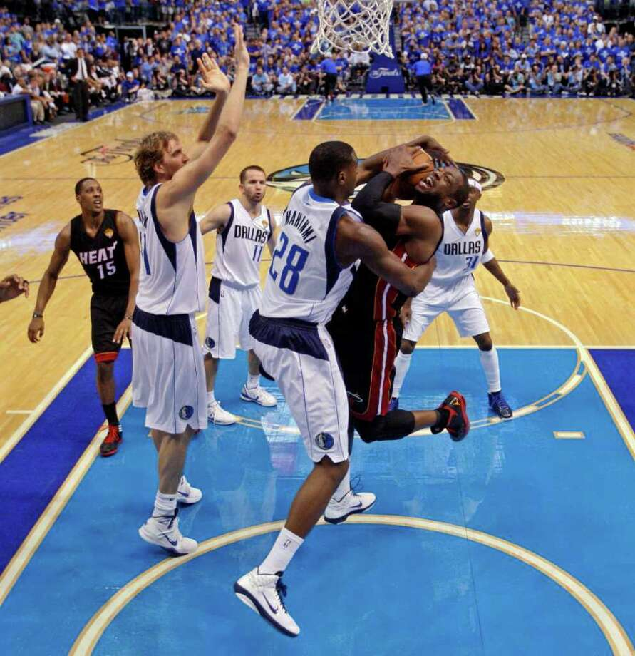 Dallas Mavericks' Ian Mahinmi (28) fouls Miami Heat's Dwyane Wade as he goes up for a shot during the second half of Game 5 of the NBA Finals basketball game Thursday, June 9, 2011, in Dallas. The Mavericks won 112-103 to take a 3-2 lead in the series. Photo: Lucy Nicholson/Associated Press