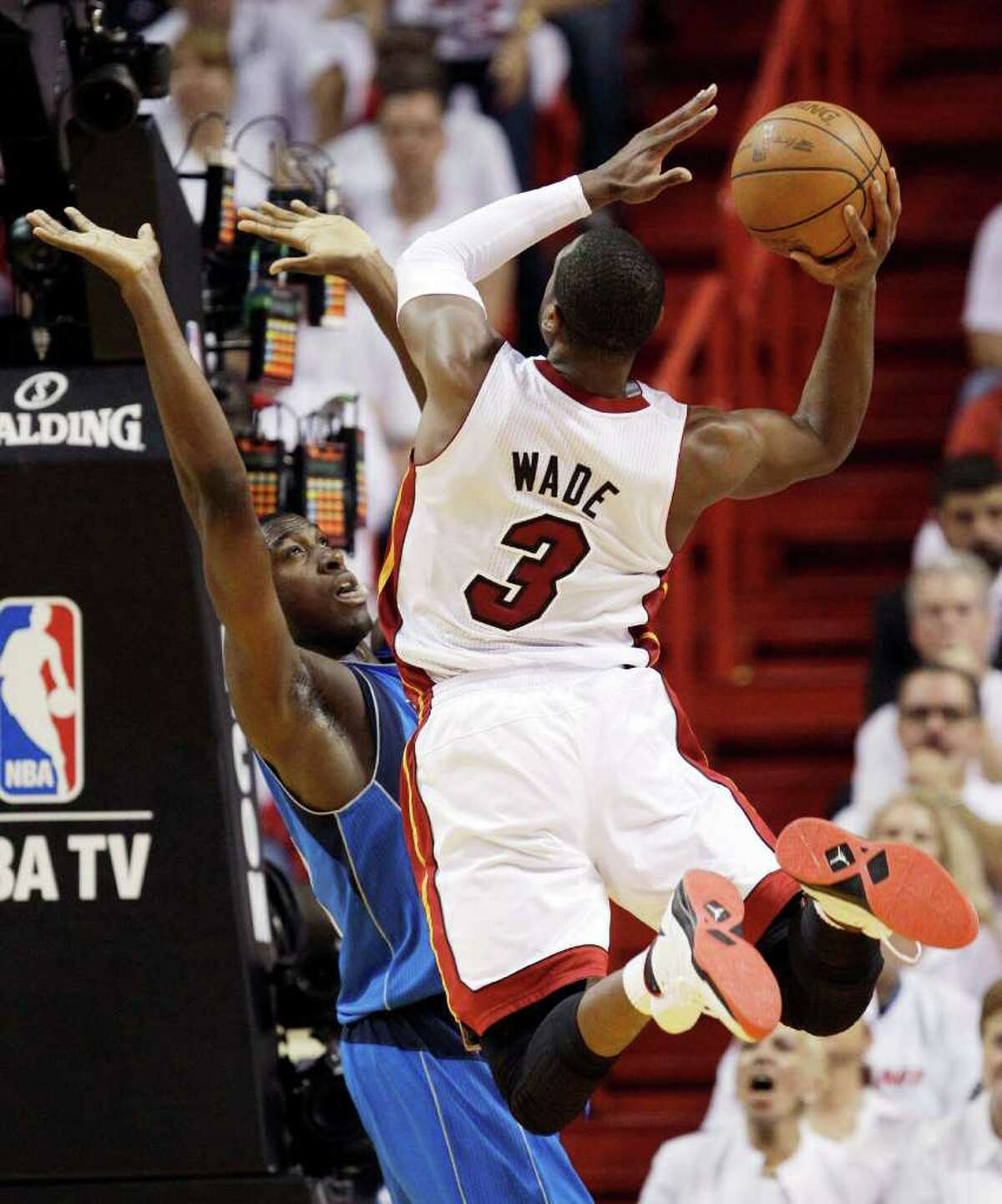 Miami Heat's Dwyane Wade (3) shoots with Dallas Mavericks' Ian Mahinmi defending during the first half of Game 6 of the NBA Finals basketball game Sunday, June 12, 2011, in Miami.