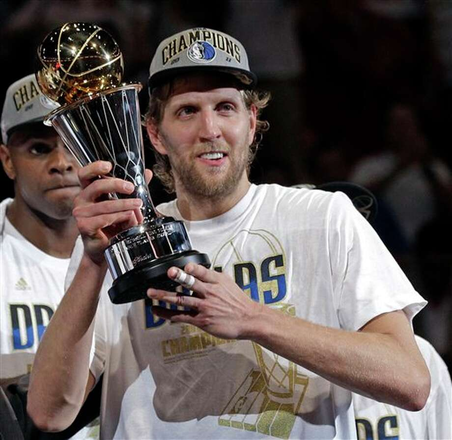 Dallas Mavericks' Dirk Nowitzki holds up the MVP trophy after Game 6 of the NBA Finals basketball game against the Miami Heat Sunday, June 12, 2011, in Miami. The Mavericks won 105-95 to win the series. (AP Photo/David J. Phillip) Photo: Associated Press